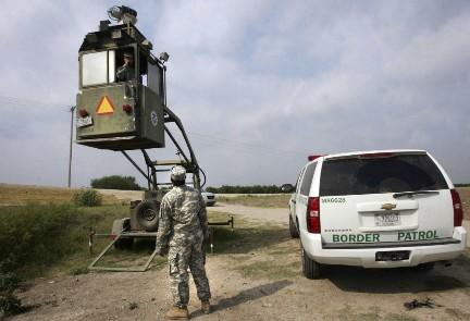 Un miembro de la Guardia Nacional observa a un compatriota de la Patrulla Fronteriza en un Skybox (Foto AP)