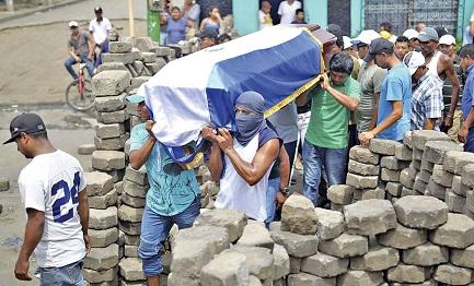 Una barricada en Masaya con manifestantes que llevan a hombros el féretro de un caído